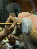 Artisan painting on clay pottery elephant with hands stock images
