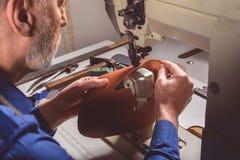 Artisan piquant une pièce en cuir de la chaussure Image stock