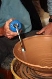 Artisan at potter's wheel. Close-up of an artisan using a blowtorch on a large clay bowl at a potter's wheel Stock Image