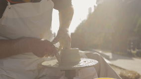 Artisan produces on pottery wheel outside workroom to create jug for water. stock video