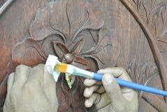 Artisan qualifié ajoutant la peau de feuille d'or au découpage du bois Image libre de droits