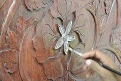 Artisan qualifié ajoutant la peau de feuille d'or au découpage du bois Photo libre de droits