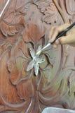 Artisan qualifié ajoutant la peau de feuille d'or au découpage du bois Photo stock