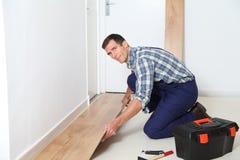 Artisan renovating house. Closeup of artisan installing flooring in room Stock Images