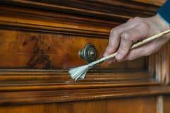 Old wood furniture restoration. Artisan restoring an old wood furniture using a brush Stock Image