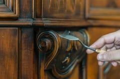 Furniture restauration. Artisan restoring an old wood furniture using a spatula Royalty Free Stock Photos