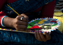 Artisan's touch. A female artisan is painting a colorful hand fan made of palm leaf Royalty Free Stock Images