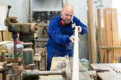 Artisan shaping timber at factory Stock Photos