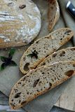 Artisan sourdough bread with basil and olives. On a wooden plate Stock Images