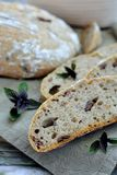 Artisan sourdough bread with basil and olives. On a wooden plate Royalty Free Stock Images