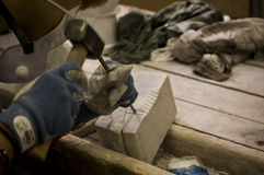 Artisan stonemason. Detail of a stonemason working with hammer and chisel Royalty Free Stock Images