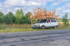Artisan ukrainien avec propre vannerie sur un toit de petite voiture faisant l'arrêt court sur un bord de la route Photos libres de droits