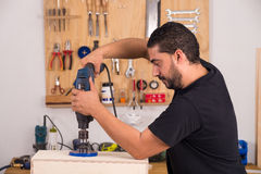 Artisan using a hole saw Stock Images