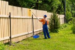 Artisan utilisant le mur en bois de peinture uniforme Image stock