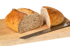 Artisan whole wheat bread on breadboard Stock Photography