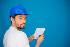 Artisan or workman taking notes. Standing in front of a blue wall with a pen and paper in his hands turning to look at the camera with a serious thoughtful Stock Photo