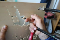 An artisan works with fretsaw Stock Images