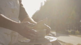 Artisan works on pottery wheel outside workroom to create jug for water. stock video footage
