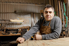 Artisan in workshop low angle view. Caucasian middle-aged artisan sitting in his workshop at workbench low angle view Royalty Free Stock Photo