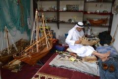 Artisanaal van Qatar dat in traditionele kleren met de hand gemaakt houten model van schepen creeert stock foto's
