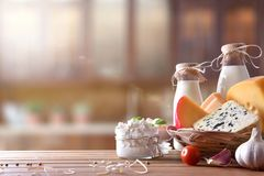 Artisanal dairy products in rustic kitchen front view. Assortment of artisanal dairy products on a wooden table in rustic kitchen. Front view. Horizontal Stock Image