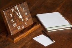 Artisanal träklocka på tabellen, med papper till beteckningssystem Arkivfoto