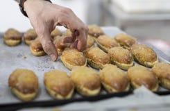 Artisanale gebakjechef-kok die cake plaatsen op metaaldienblad stock foto's