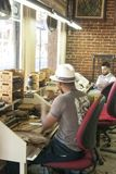 Artisans de cigares dans le petit travail de magasin de cigare photographie stock