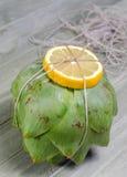 Artischocke mit vooking Schnur und Zitrone Stockbilder