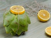 Artischocke mit vooking Schnur und Zitrone Stockfotos