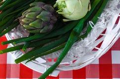 Artisjok, groene ui en koolraap in witte houten mand met stro stock foto