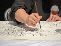 Artist's hand drawing Asian artwork on a canvas using ink pen stock image