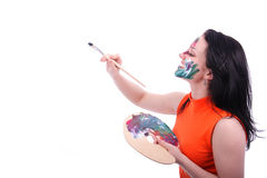 Artist. Young girl with a brush, a palette and the painted face on a white background Royalty Free Stock Photos