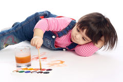 Artist. Cute little baby painting lying on the floor Royalty Free Stock Photography