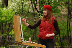 Artist. Young attractive artist is painting outdoor Stock Photography