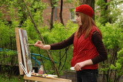 Artist. Young attractive artist is painting outdoor Royalty Free Stock Photos