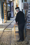 Artist in the alley of shops and art galleries in Tzfat Stock Images