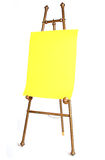 Artist antique easel. Antique brass artist easel with bright yellow paper royalty free stock photography