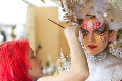 Artist Applies Body Paint To Female Model's Face At Festival Stock Photo