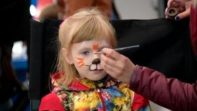 Artist applies funny cat make-up for girl age 7 years stock video
