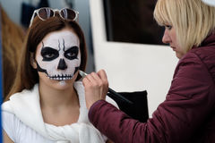 Artist applies skull make-up for guest Royalty Free Stock Image