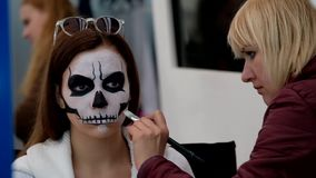 Artist applies skull make-up for guest stock video footage