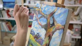 Artist is applying finish strokes on landscape pictures, close-up of canvas. Painter is painting beautiful landscape by oil paints in art studio, close-up of stock footage