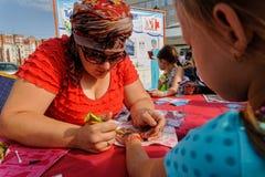 Artist applying henna tattoo on girl hand. Tyumen Stock Photos