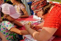 Artist applying henna tattoo on girl hand. Tyumen Stock Photo