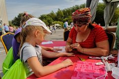 Artist applying henna tattoo on girl hand. Tyumen. Tyumen, Russia - August 26, 2016: Open Day of Sberbank for children. Artist applying henna tattoo on girl hand stock photography