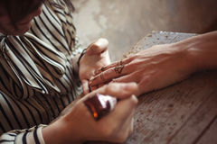 Artist applying henna tattoo on women hands Royalty Free Stock Images