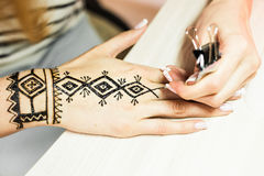 Artist applying henna tattoo on women hands. Mehndi is traditional Indian decorative art. Close-up Royalty Free Stock Photo
