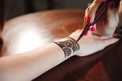 Artist applying henna tattoo on women hands. Mehndi is traditional Indian decorative art. Close-up stock image