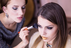 Artist Applying Make up to Pretty Female Model Stock Photo